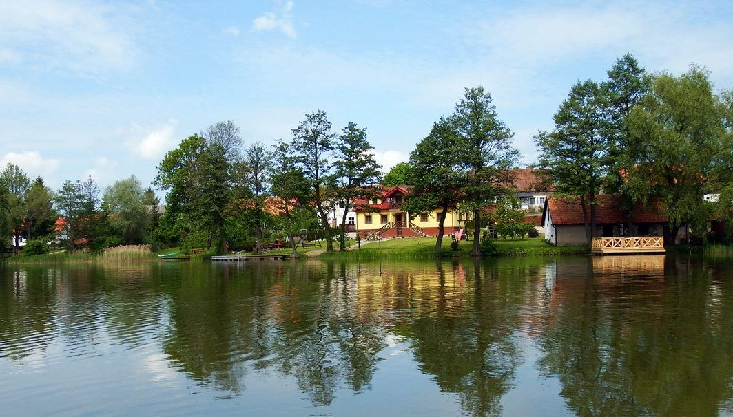 Widok z jeziora na brzeg z budynkiem kuxni i domem noclegowym