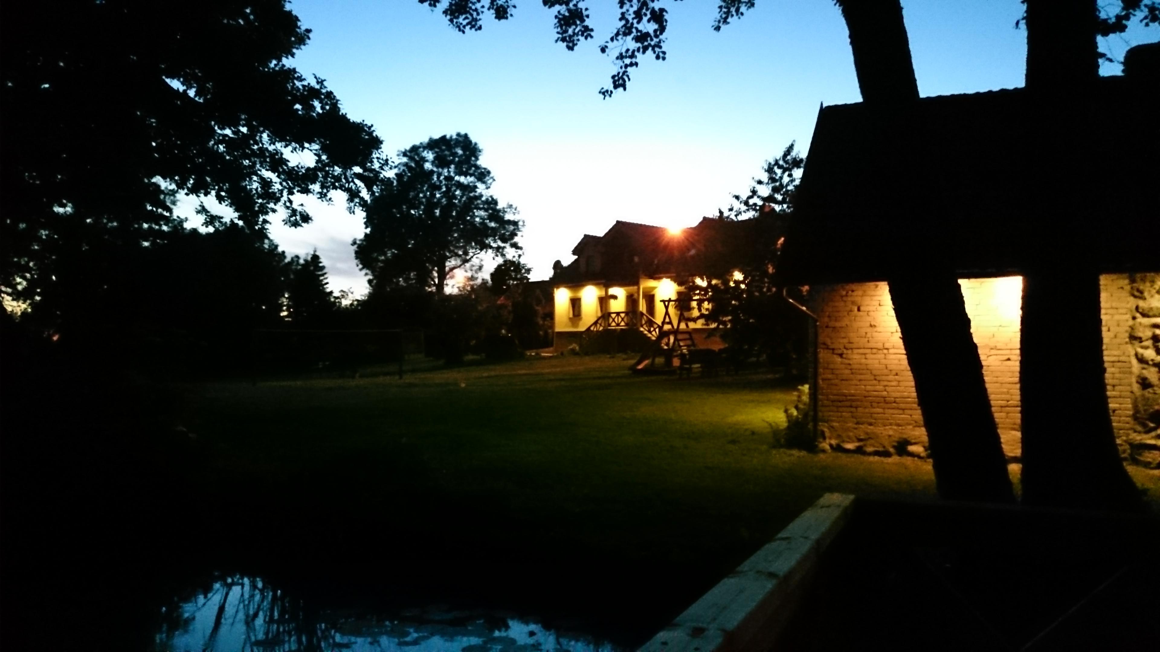 Widok na dwa oświetlone budynki kużni i dom noclegowy