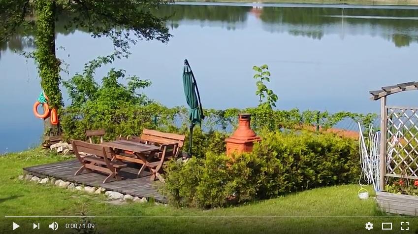 brzeg jeziora, woda, las, stoły biesiadne z grillem, koło ratunkowe na drzewie