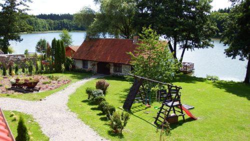 Widok na budynek kuźni, na palc zabaw i jezioro z lasem
