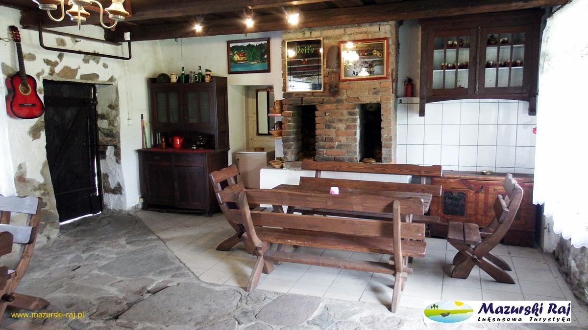 Widok na stoły biesiadne, szafę i obrazy na ścianach